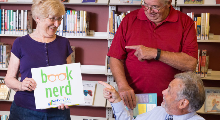 "Book Club member holds a Marysville Public Library ""book nerd"" sign"